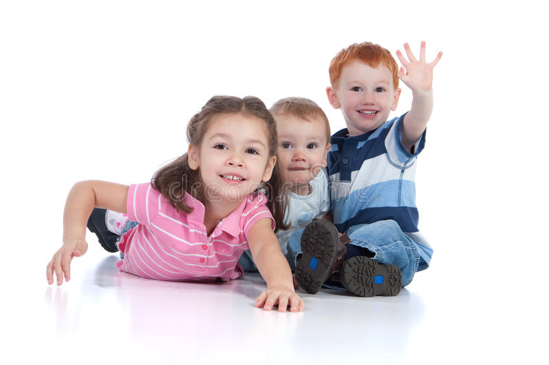 Happy and excited kids. Three happy kids sitting and lying on floor and waving. Isolated white background, foreground reflection