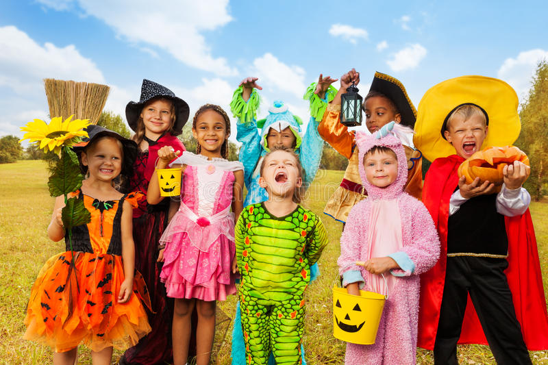 Happy excited kids in Halloween costumes. Stand close on green grass of the field stock photography