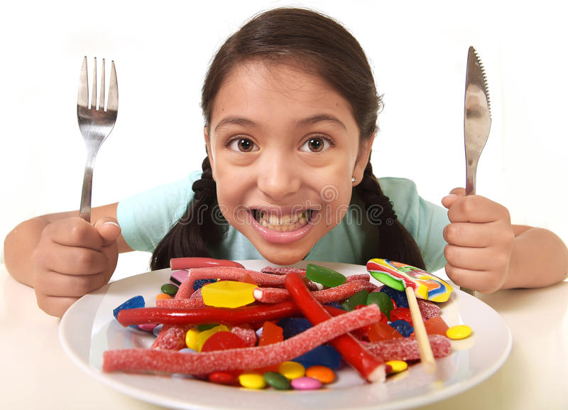 Happy excited Latin female child holding fork and knife sitting at table ready for eat a dish full of candy royalty free stock photography