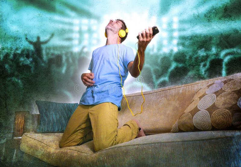Happy and excited man jumping on sofa couch listening to music with mobile phone and headphones playing air guitar crazy imagine. Young happy and excited man stock images