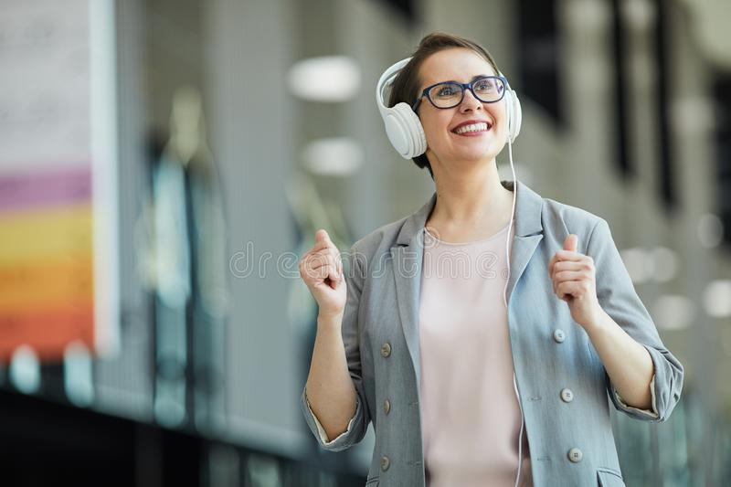 Happy middle-aged lady listening to music stock photos