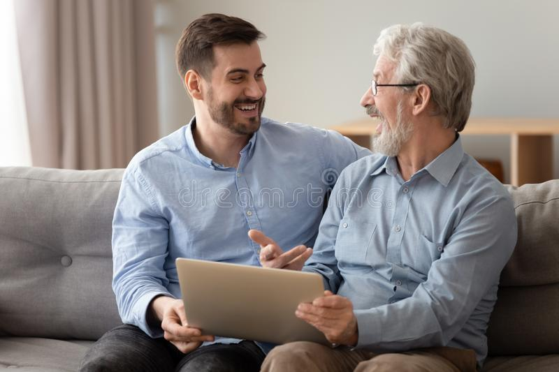 Happy excited old father and young son talking using laptop. Happy excited two generation men family, old senior father and smiling young adult grown son talking royalty free stock photos