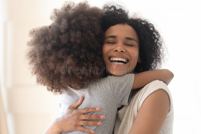 Happy excited single african american mother cuddling little preschool daughter. royalty free stock image