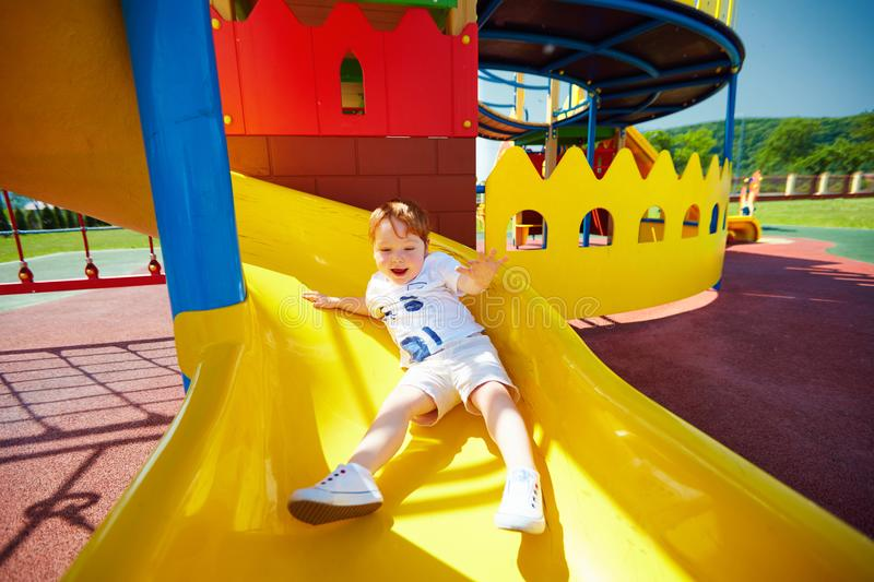 Happy excited toddler baby boy sliding in colorful playground at summer day stock photo