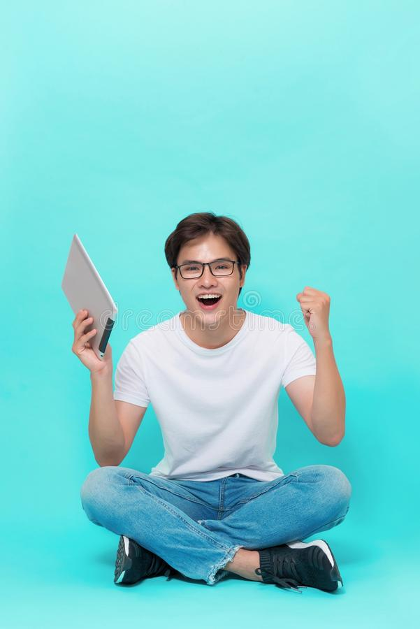 A happy excited young asian man with a digital tablet and celebrating success stock image