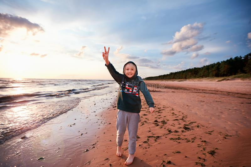 Happy excited young boy having fun on a sandy autumn beach, raising up victory sign fingers stock image