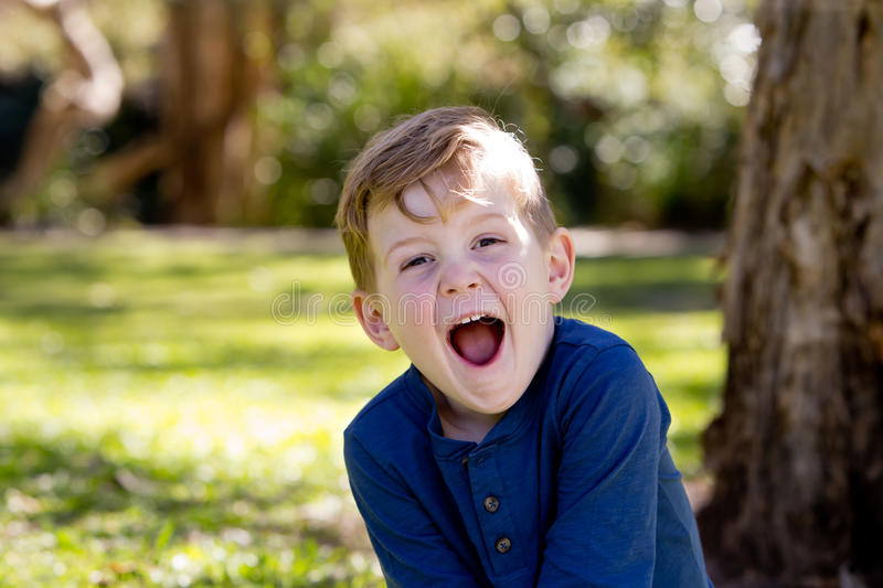 Happy and excited young boy sitting crossed legged against tree royalty free stock photos