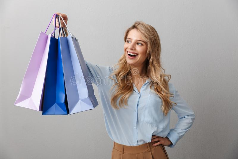 Happy excited young pretty blonde business woman posing  grey wall background holding shopping bags. Image of a happy excited young pretty blonde business woman royalty free stock image