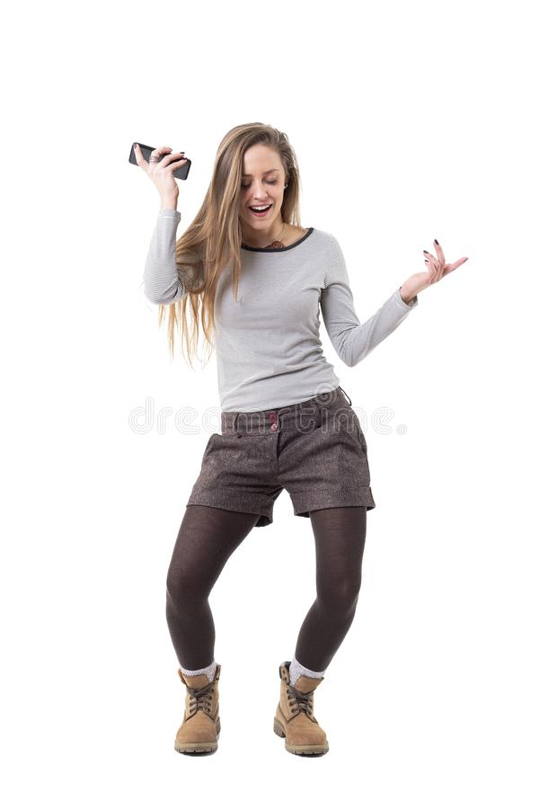 Happy excited young woman dancing and listening music on mobile phone loud speaker. stock photo