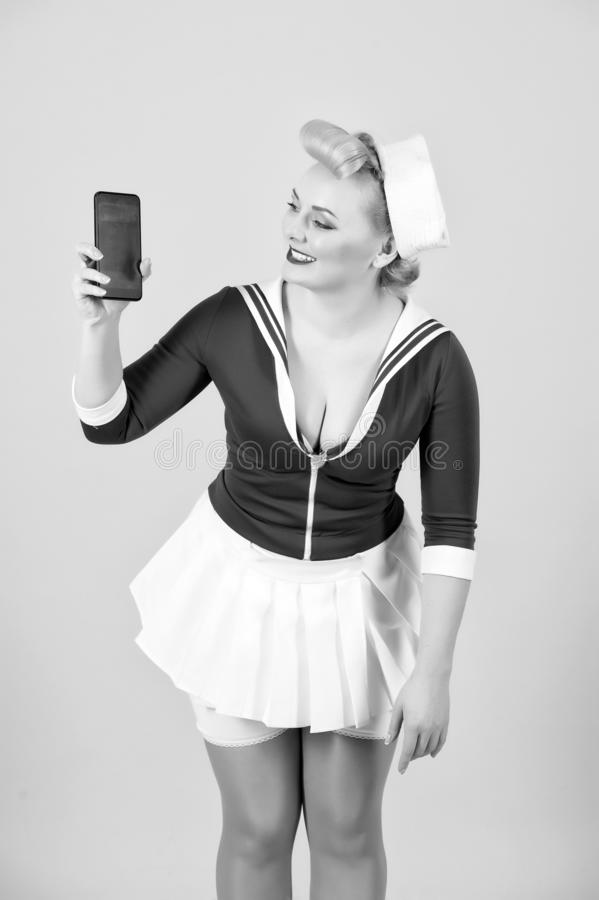 Happy excited young woman dressed in pin-up style looks at mobile phone over gray background. Vintage girl and technology stock photography