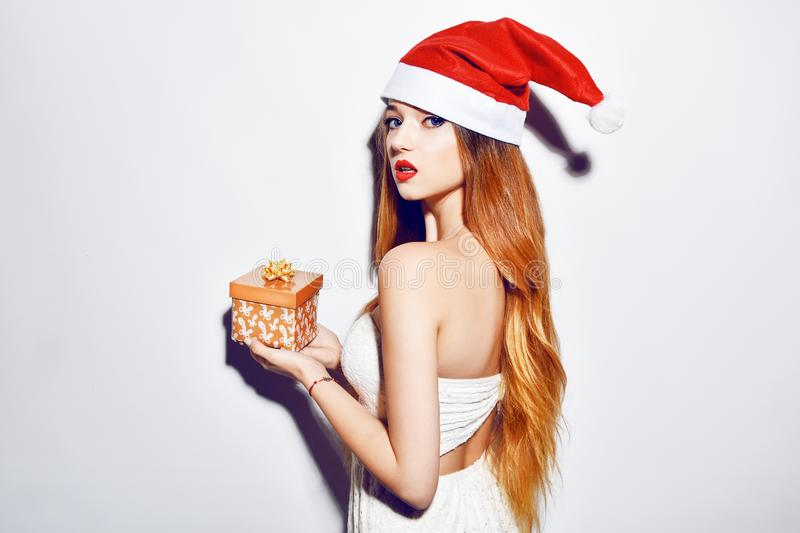 Happy excited young woman in santa claus hat with gift box over white background. Long hair. red lips, white dress. stock photos