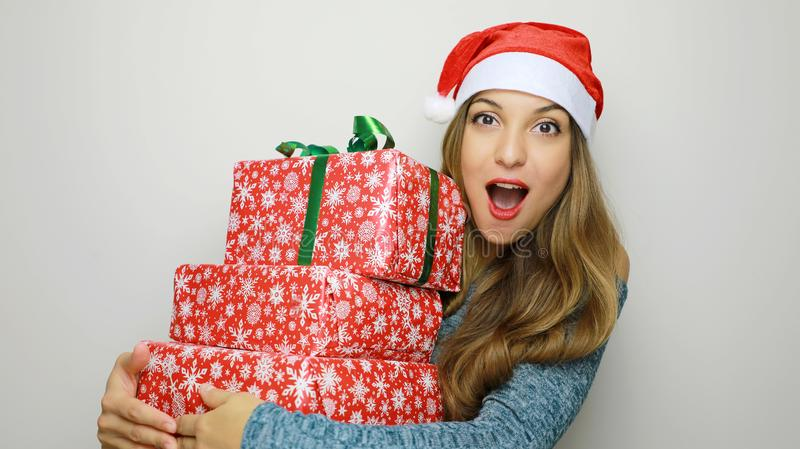 Happy excited young woman in santa claus hat with gifts box over stock photos
