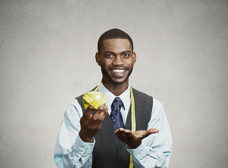 Happy executive advising on healthy diet, holding green apple stock image