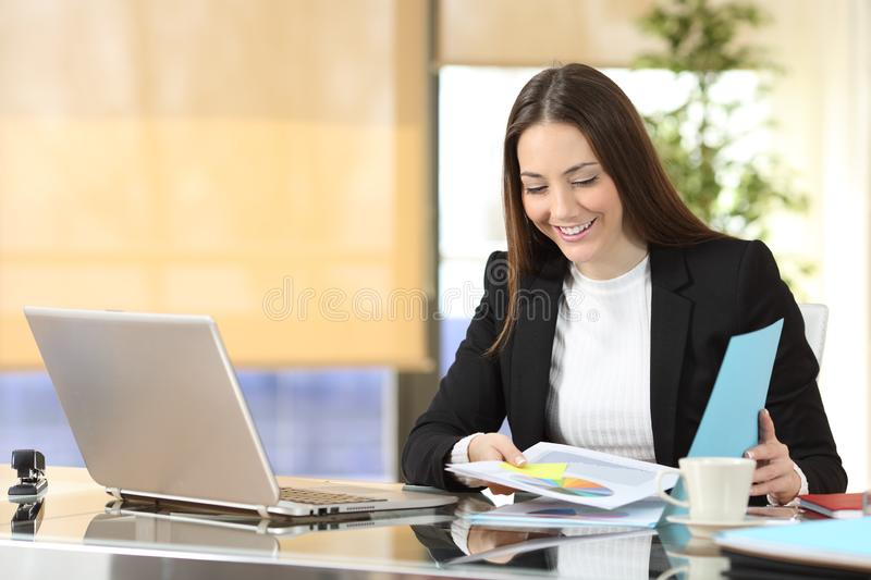 Happy executive checking documents at office royalty free stock photography