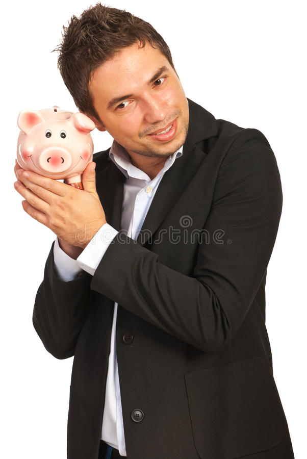 Happy executive listen to piggy bank