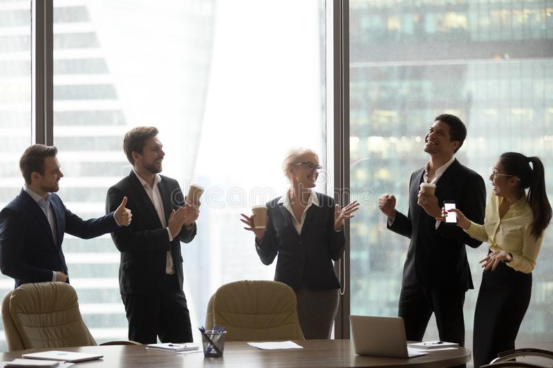 Happy executive team dancing to music having fun in office stock image