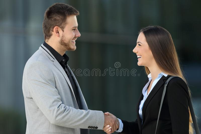 Happy executives meeting and handshaking on the street. Side view of two happy executives meeting and handshaking on the street with an office building in the royalty free stock photography