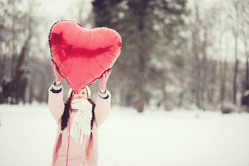 Happy exited girl with Valentine heart balloons outdoor. Valentine`s day concept. Copy space. stock image