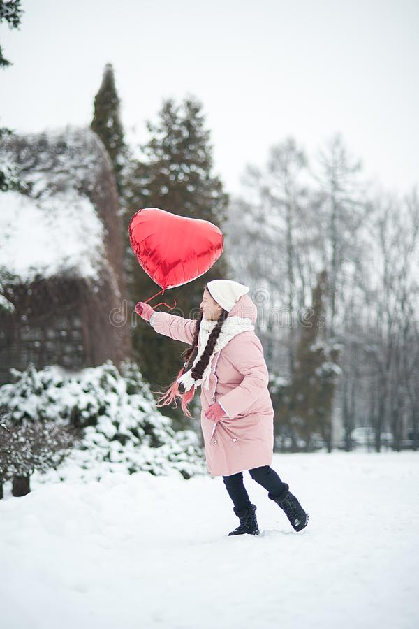 Happy exited girl with Valentine heart balloons outdoor. Valentine`s day concept. Copy space. royalty free stock images