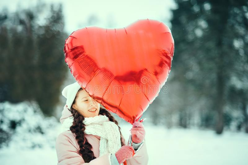 Happy exited girl with Valentine heart balloons outdoor. Valentine`s day concept. Copy space. royalty free stock photo