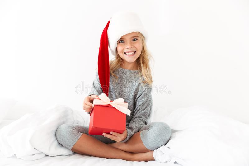 Happy exited little girl in Santa`s hat holding gift box, lookin royalty free stock photos