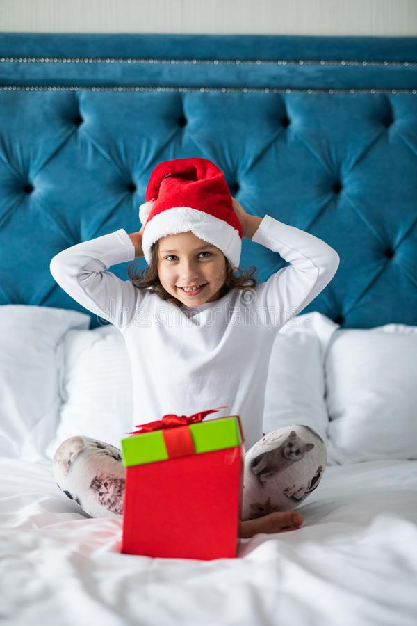 Happy exited little girl in Santa`s hat holding gift box, looking at camera excited while sitting on bed stock photo