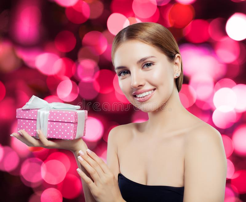 Happy exited woman holding pink gift and smiling royalty free stock photo