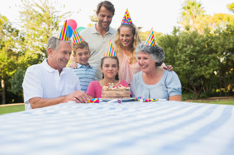 Happy extended family celebrating little girls birthday. Outside at picnic table stock image