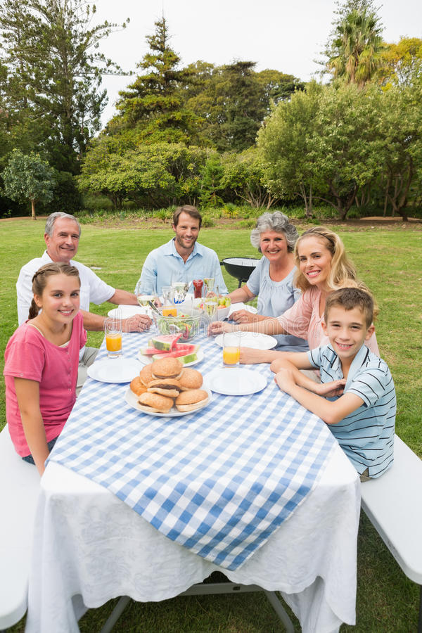 Happy extended family having dinner outdoors at picnic table royalty free stock photos