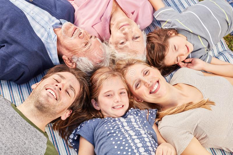 Happy extended family lies in circle stock photo