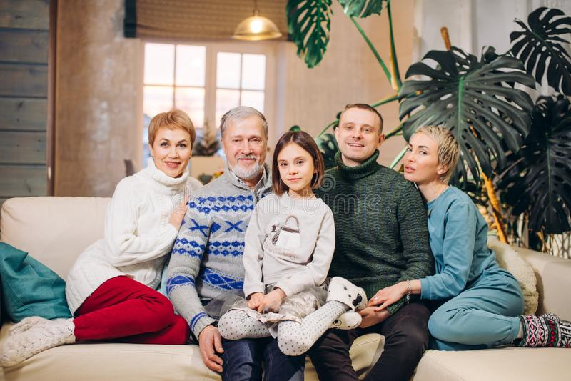 Happy extended family sitting on sofa together stock photo