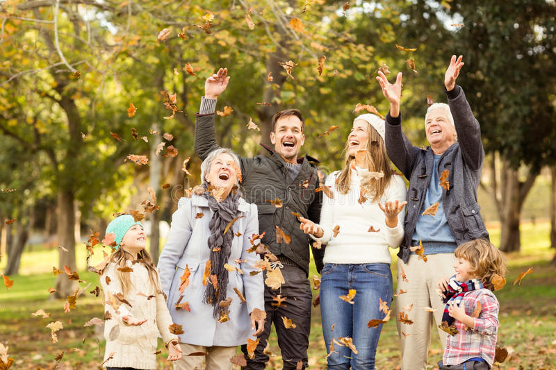 Happy extended family throwing leaves around royalty free stock image