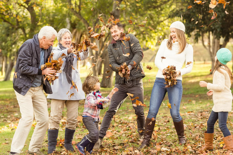 Happy extended family throwing leaves around stock photos