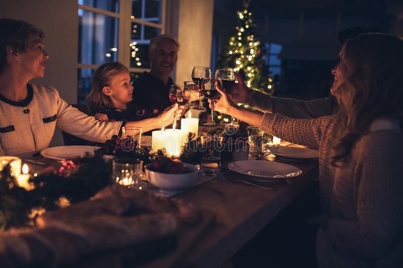 Happy extended family having christmas dinner at home. Happy extended family toasting drinks during christmas dinner at home in the living room. Family stock photography