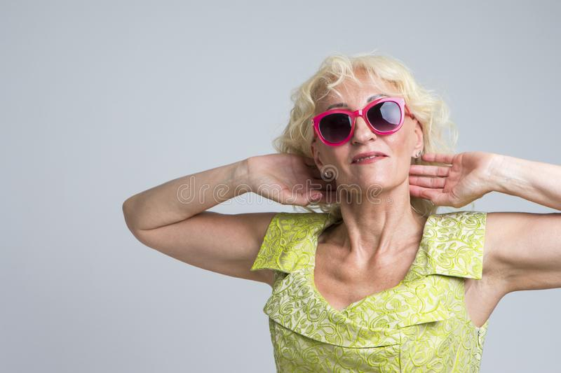 Happy Extravagant Mature Caucasian Blond Woman in Red Sunglasses Posing in Green Dress with Hands Lifted and Folded Behind stock photos