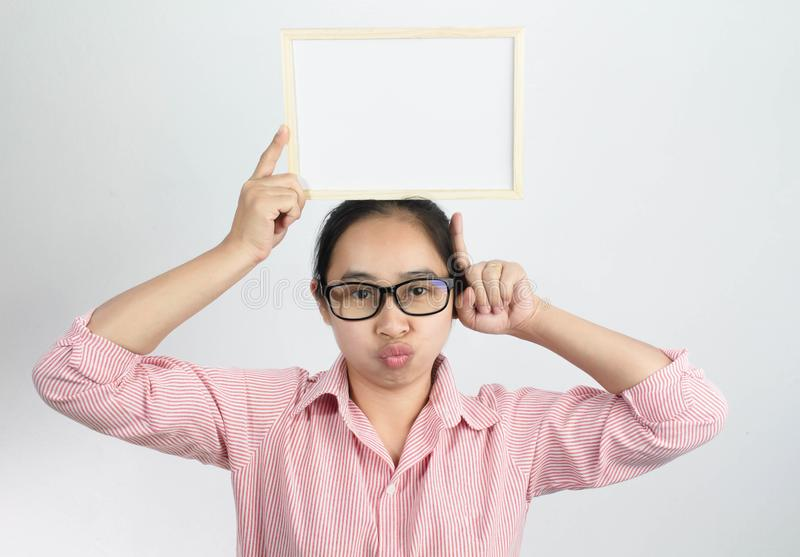 Happy face Asian woman holding blank white board on her head and show finger pointing  on a white background. Copy Placed stock photos
