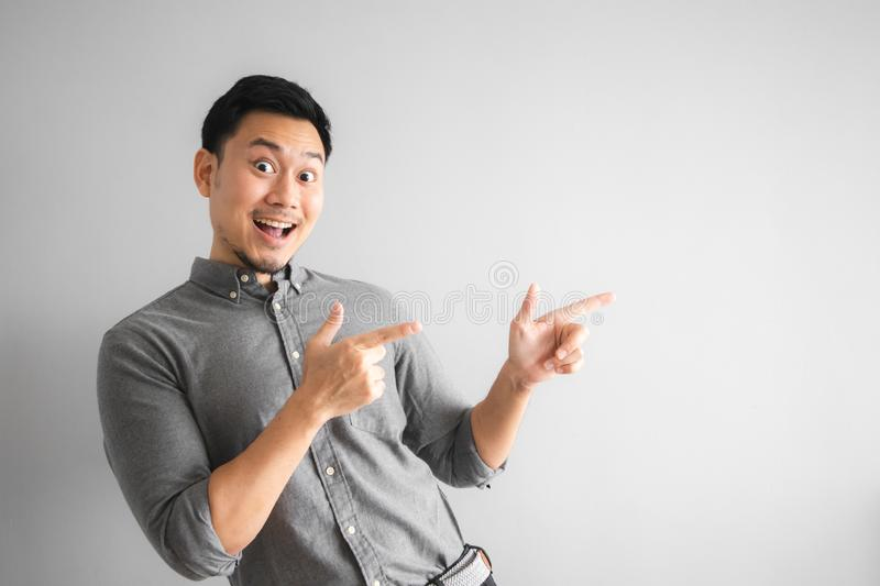 Happy face of funny good looking man with hand sign pointing royalty free stock photo