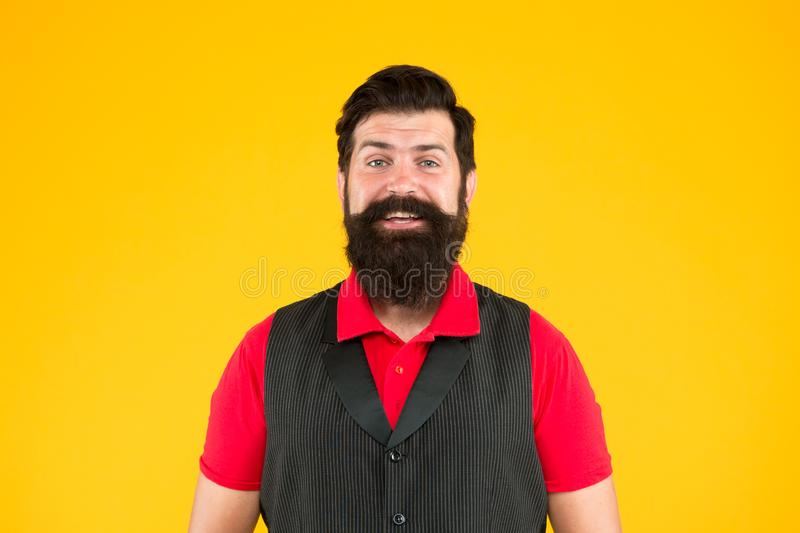 Happy face. Restaurant cafe staff wanted. Man bearded hipster with mustache wear vest shirt uniform yellow background. Shop staff concept. Salesman career stock photography