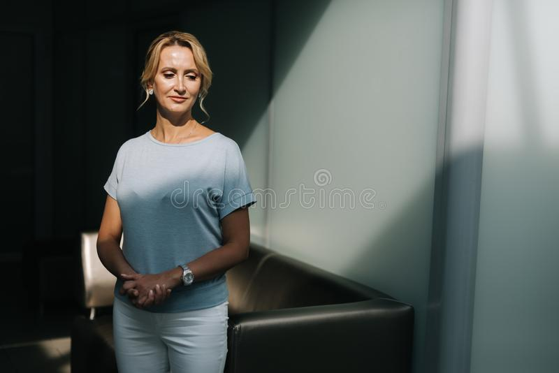 Happy faced middle aged woman lady is looking away. Portrait of sensual young woman posing by the black couch. Beautiful well-groomed female looking away stock photography