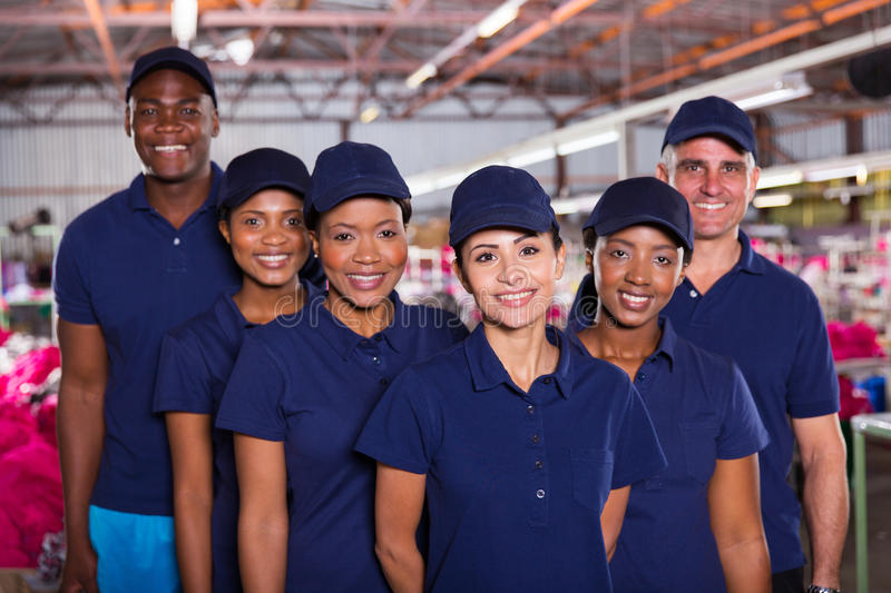 Happy factory workers. Group of happy clothing factory workers inside production area royalty free stock photography