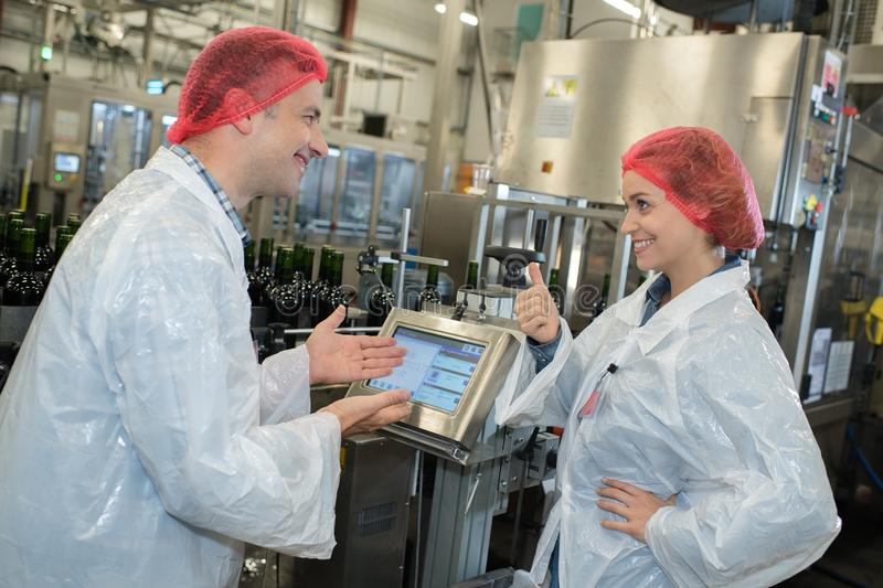 Happy factory workers talking. Factory stock image