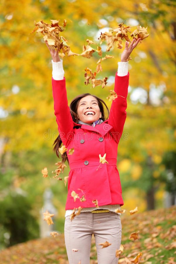 Happy fall woman throwing leaves royalty free stock photo