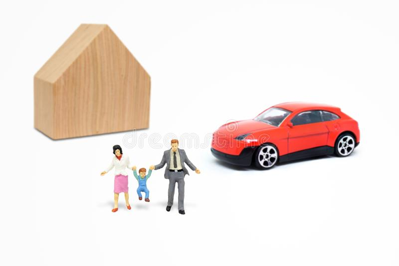 Miniature people as happiness family with wooden house and red car model toy in background. royalty free stock photography