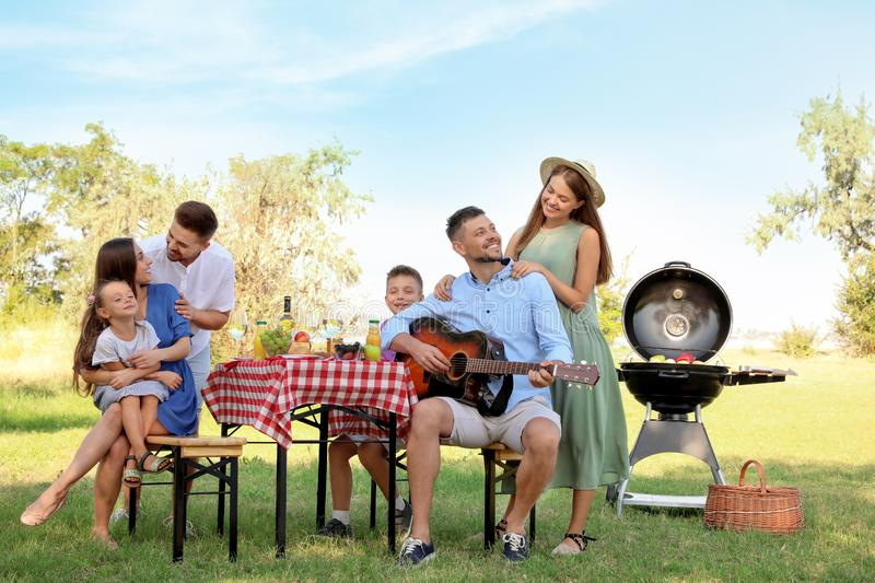 Happy families with little children having picnic. In park royalty free stock image