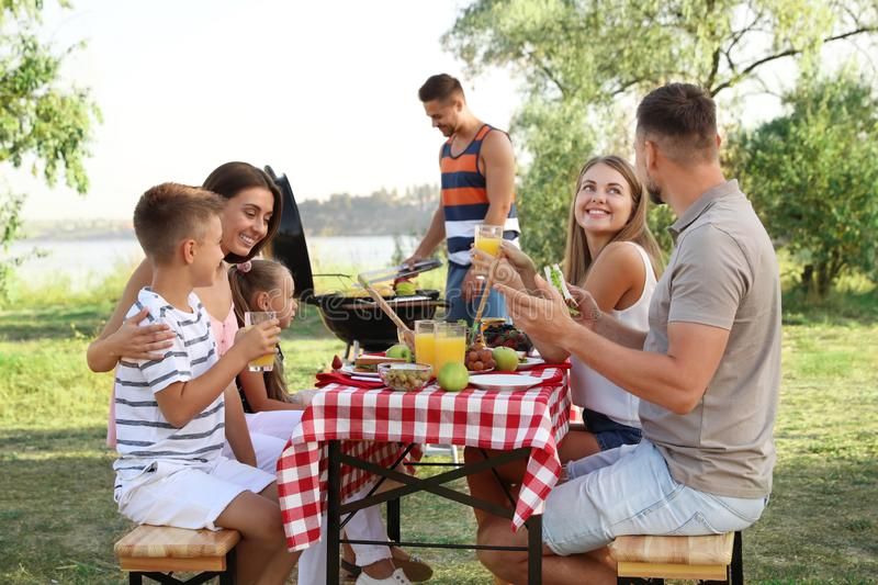 Happy families with little children having picnic stock image