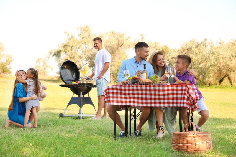 Happy families with little children having picnic. In park stock photography