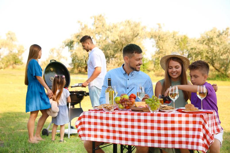 Happy families with little children having picnic stock images