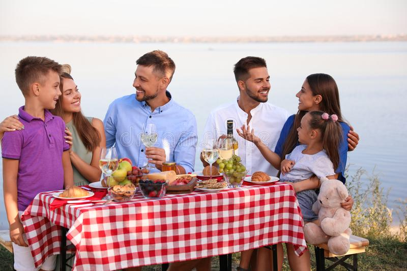 Happy families with little children at picnic table stock images