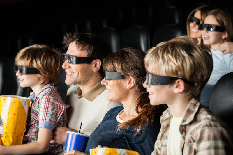 Happy Families Watching 3D Movie In Theater. Happy families with snacks watching 3D movie in cinema theater stock photos