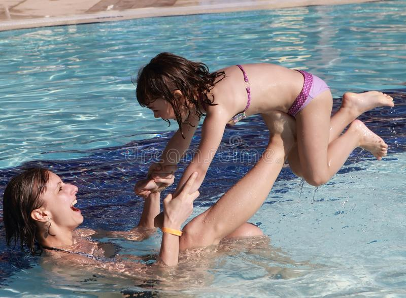 Happy family playing in the pool